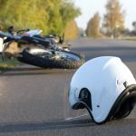 motorcycle and helmet laying on the street